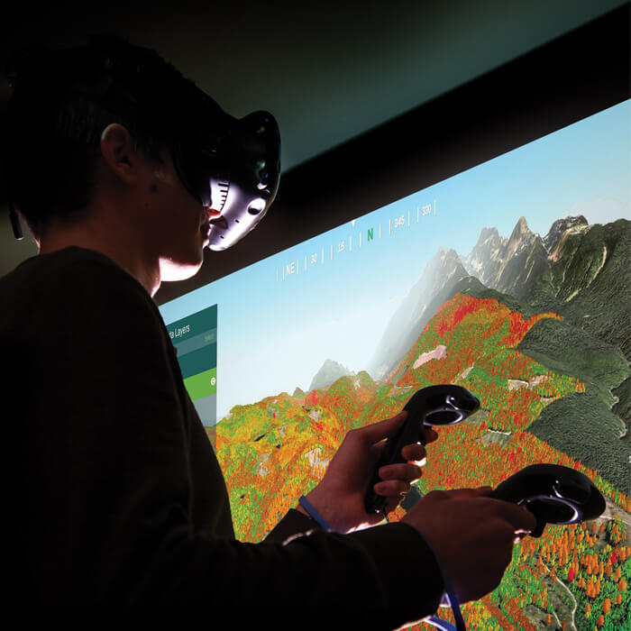 Virtual Reality. Person using TimberOps VR goggles with screen of what they are viewing behind them
